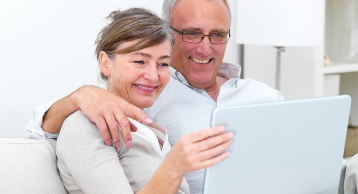 man and woman on couch looking at a laptop screen