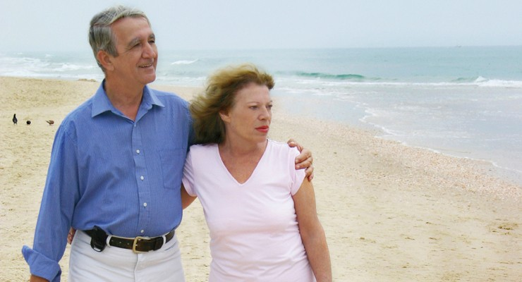 man and woman walking on a beach.